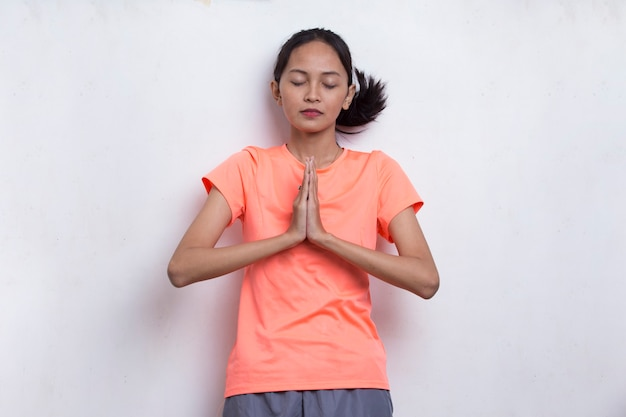 白い背景の瞑想をリラックスしてヨガをやっている若い美しいアジアのスポーツ女性