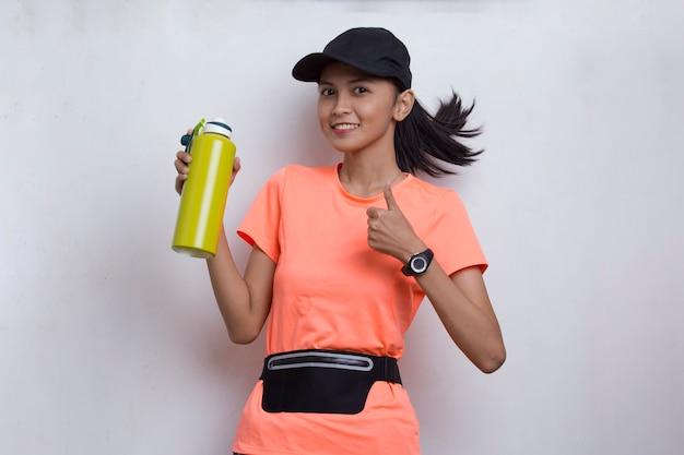 白い背景の上のトレーニングの後に水を飲む若い美しいアジアのスポーツ女性 Premium写真