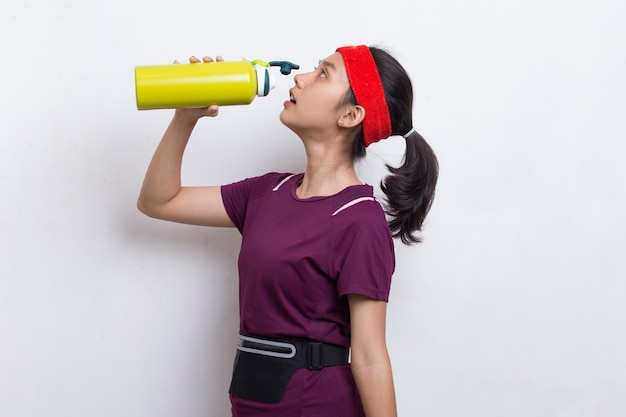 Young beautiful asian sport woman drinking water after workout on white background