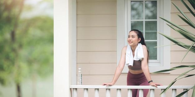 家のテラスに立って、運動後にリラックスできる若い美しいアジアのスポーツウーマン。