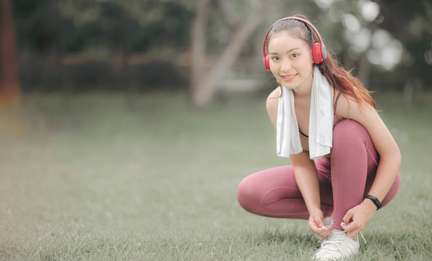 Young beautiful asian sportswoman with headphone tying shoelaces and preparing to run, smiling and looking at camera.