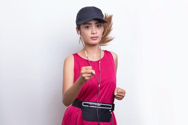 白い背景で実行している若い美しいアジアのスポーティな女性