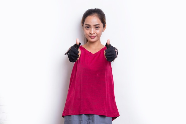 白い背景の上の親指をokジェスチャーを示す若い美しいアジアのスポーティな女性