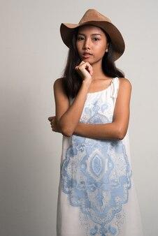 Young beautiful asian teenage girl as tourist thinking