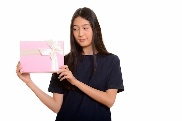 Молодая красивая азиатская девочка-подросток угадывает подарочную коробку