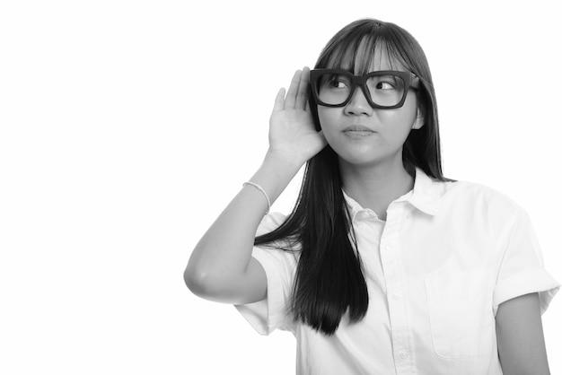 Молодая красивая азиатская девочка-подросток изолирована у белой стены в черно-белом