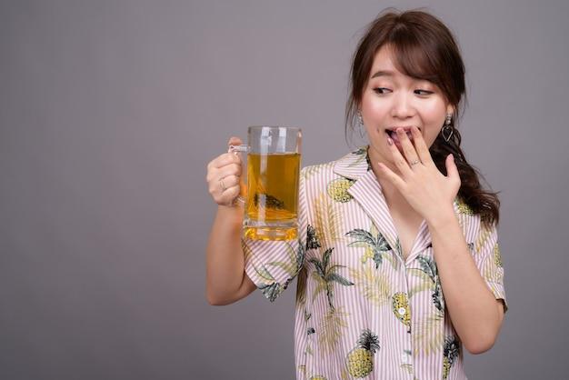 맥주 잔을 들고 젊은 아름 다운 아시아 관광 여자