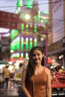 チャイナタウンの夜に若い美しいアジア観光女性