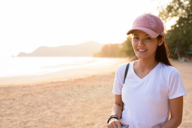 Молодая красивая азиатская туристическая женщина отдыхает на пляже