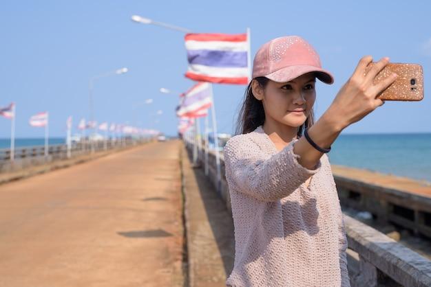 桟橋でselfieを取って若い美しいアジア観光女性