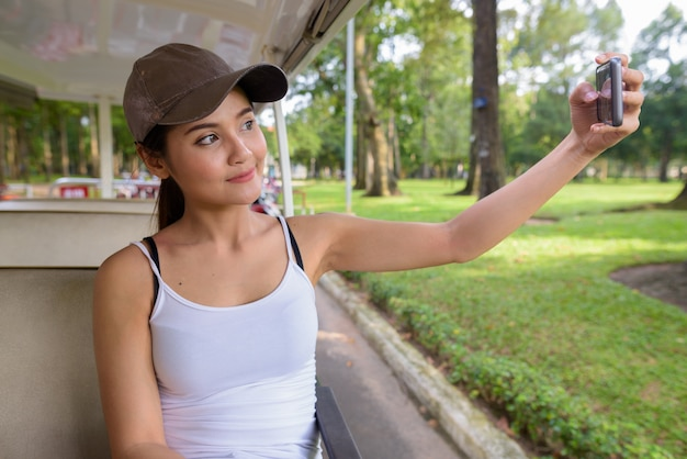 Young beautiful asian tourist woman taking selfie with phone