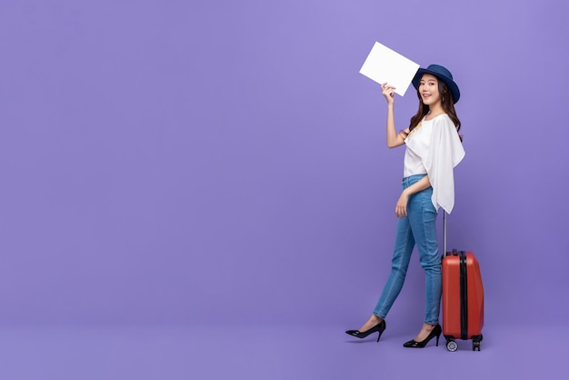 Young beautiful asian tourist woman with baggage holding blank white paper