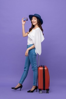 Young beautiful asian tourist woman with baggage holding credit card