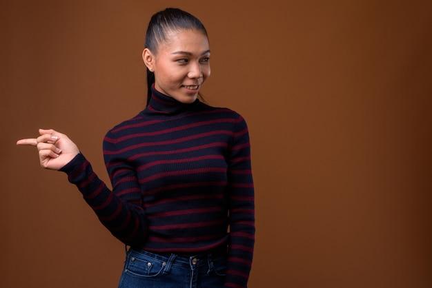 茶色の背景の若い美しいアジアのトランスジェンダーの女性