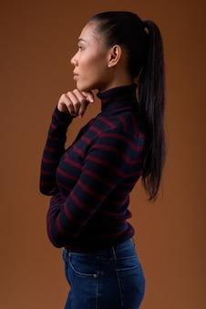 Молодая красивая азиатская трансгендерная женщина на коричневом фоне