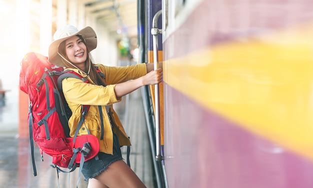 배낭은 교외 기차역의 플랫폼에서 기차를 타고 웃고 앞을보고 젊은 아름 다운 아시아 여행자