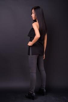 검은 벽에 젊은 아름 다운 아시아 여자