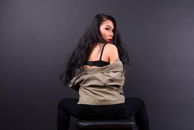 Молодая красивая азиатская женщина у черной стены