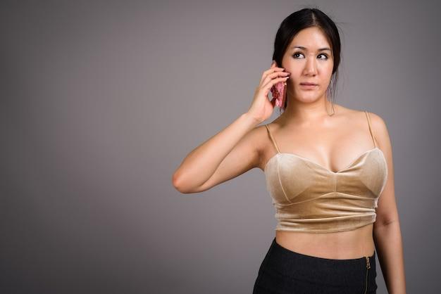 灰色の壁に対して若い美しいアジアの女性