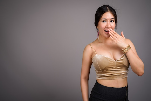 Молодая красивая азиатская женщина против серой стены