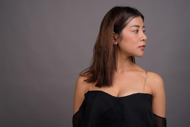 Молодая красивая азиатская женщина против серого