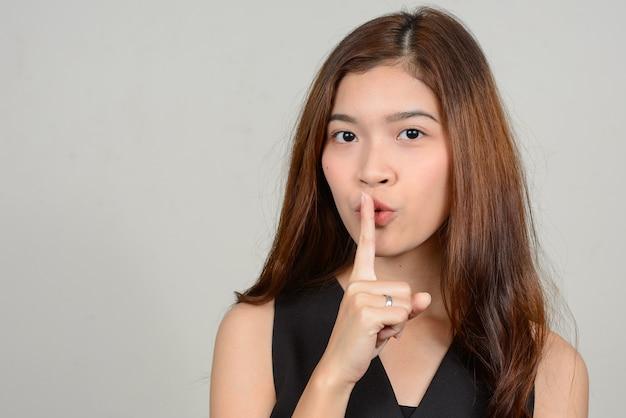 Молодая красивая азиатская женщина против белого пространства