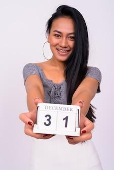 白い壁に対して若い美しいアジアの女性