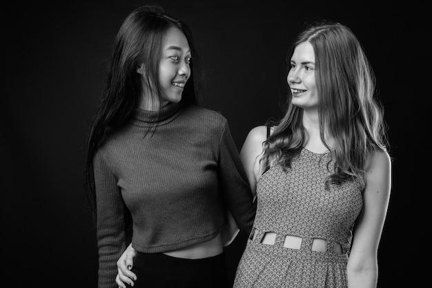 黒と白で一緒に若い美しいアジアの女性と若い美しいスカンジナビアの女性