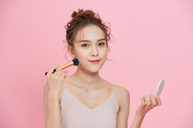 젊은 아름다운 아시아 여성이 화장을 하고 거울을 보고 있다