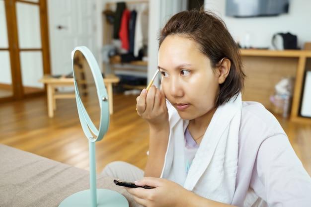 適用する若い美しいアジアの女性は、自宅で鏡の前を構成します。化粧品の塗装