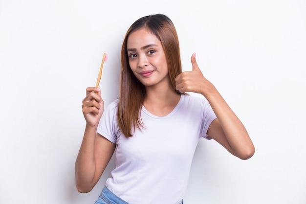 Молодая красивая азиатская женщина чистит зубы щеткой на белом фоне