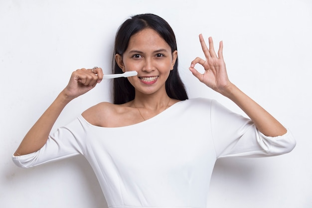 Young beautiful asian woman brushing her teeth isolated on white background