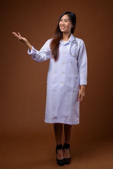 茶色の背景の若い美しいアジアの女性医師