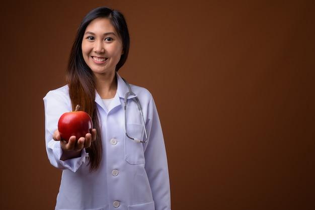 Молодая красивая азиатская женщина-врач на коричневом фоне