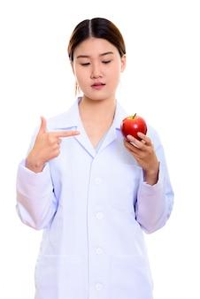 若い美しいアジアの女性医師を押しながら赤いリンゴを指して