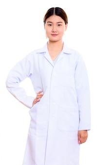Молодая красивая азиатская женщина-врач, стоя с рукой на бедре