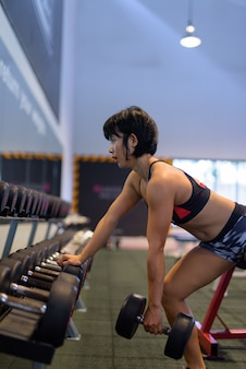Young beautiful asian woman doing dumbbell row in gym