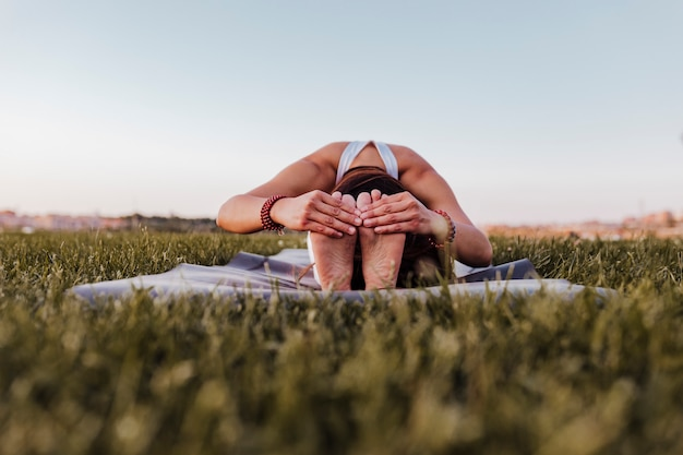 Young beautiful asian woman doing yoga in a park at sunset. yoga and healthy lifestyle concept
