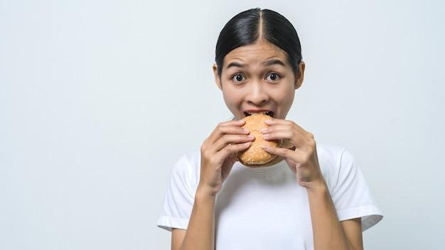 ハンバーガーを食べて、カメラを探している若い美しいアジアの女性。