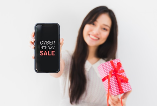 Young beautiful asian woman hands holding gift box and smartphone with cyber monday screen