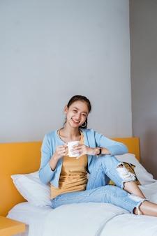Молодая красивая азиатская женщина с кофе в уютной спальне