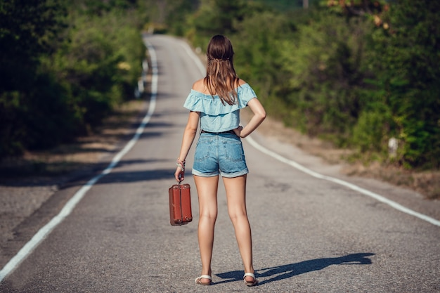 Young beautiful asian woman in hippy style. travels by hitchhiking. road in the mountains. the idea and concept of summer holidays and freedom