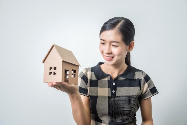 Молодая красивая азиатская женщина держа дом в ее руках, черные волосы.
