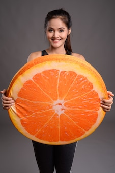 大きなオレンジを保持している若い美しいアジアの女性