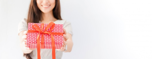 Young beautiful asian woman holding gift box in hand.