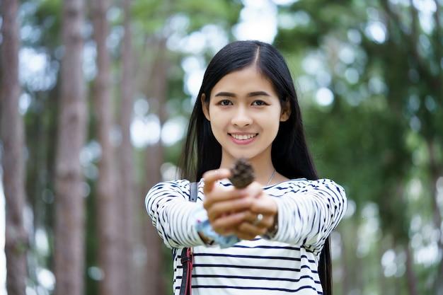 松の森で松の実を保持している若い美しいアジアの女性。