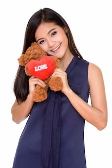 Молодая красивая азиатская женщина держит плюшевого мишку с сердцем