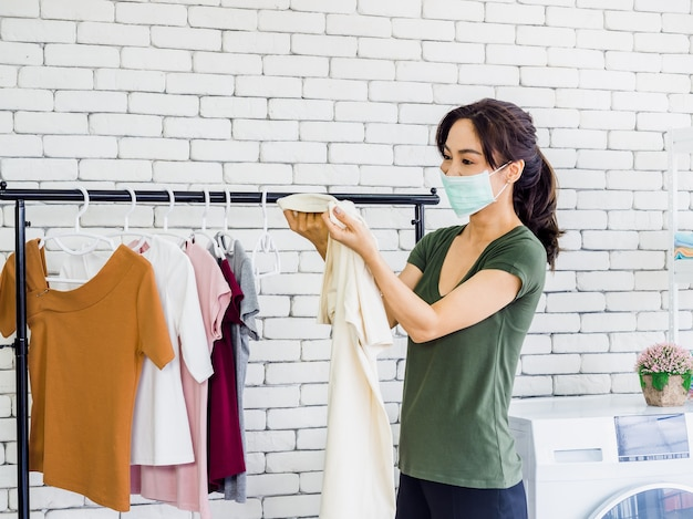 Young beautiful asian woman, housewife wearing casual cloth and protective face mask holding shirt, checking dirty stain on it after washing