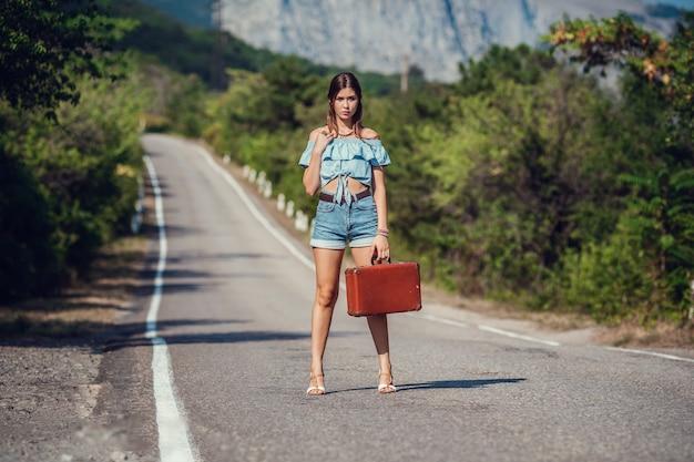 Молодая красивая азиатская женщина в стиле хиппи. путешествует автостопом. дорога в горах. идея и концепция летнего отдыха и свободы