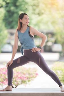 健康的な生活を維持するためにcovid-19パンデミックの間に暑いでトレーニングの前にストレッチをしているスポーツ衣装の若い美しいアジアの女性。健康な若い女性のストレッチとトレーニングにウォーミングアップ